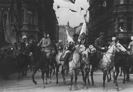 Kenraali Mannerheimin esikunta lippuineen asettuu Pohjoisesplanadin ja Kluuvikadun risteykseen vastaanottamaan ohimarssia.