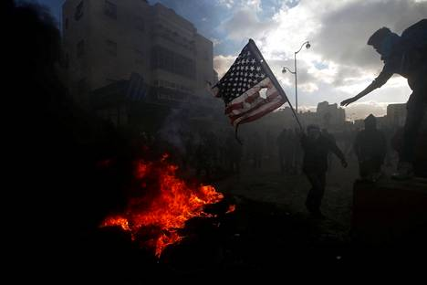 Palestiinalainen mielenosoittaja valmistautuu polttamaan Yhdysvaltojen lipun Länsirannalla.