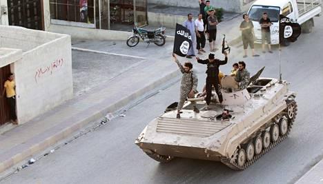 Isis-taistelijat heiluttivat mustaa lippuaan Raqqan kadulla 30.6.2014.