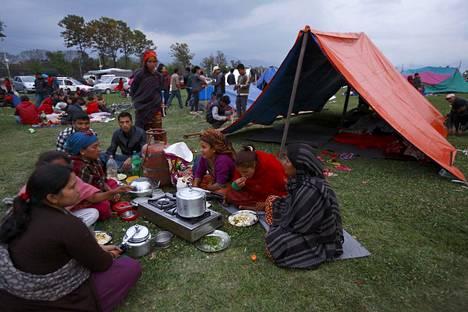 Perhe istui illallisella aukealle paikalle pystytetyn hätämajoituksensa edessä Kathmandussa illalla.