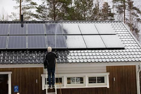 Autotallin katolle asennettiin 18 aurinkopaneelia. Heinonen puhdistaa paneelit lumesta ja jäästä vedellä.