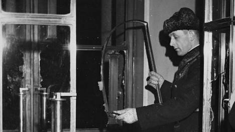 Eduskuntatalon oven edessä räjähti trotyylipanos 14.2.1950. Viranomainen tutkimassa räjähdyksen jälkiä.