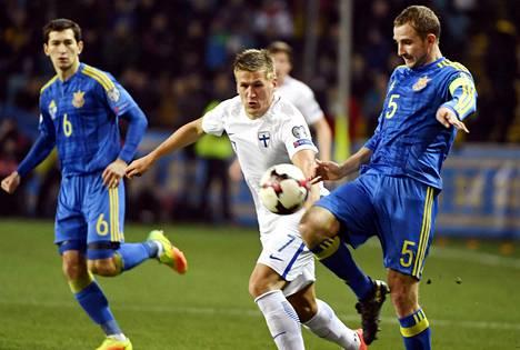 Suomen kärkimies Robin Lod (kesk.) kamppaili pallosta Ukrainan pakkien kanssa.