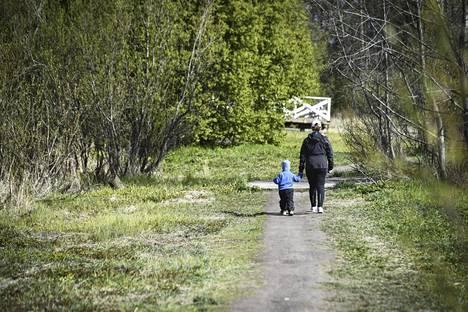 Äiti ja lapsi kävelivät Helsingissä Vantaanjoen varrella.