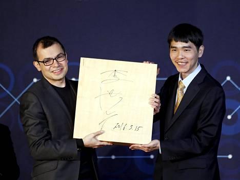 AlphaGon kehittäjä Demis Hassabis (vasemmalla) ja tekoälylle 4-1 hävinnyt suurmestari Lee Sedol poseeraavat yhdessä pelilaudan kanssa, jolla historiallisesti merkittävät ottelut pelattiin.