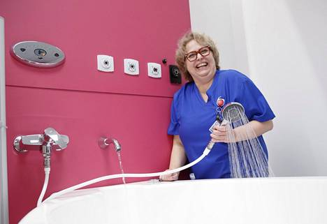 Kätilö Marjaana Kuusisto testaa potilashuoneessa sijaitsevan ammeen suihkua. Toimii!