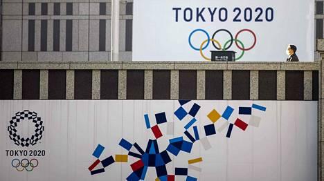 Jalankulkija ohitti olympialaismainoksen Tokiossa tammikuussa.