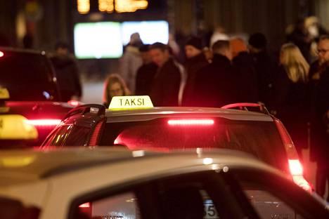 Takseja ja taksin jonottajia Helsingin Rautatieaseman taksitolpalla marraskuussa 2018.