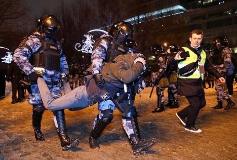 Poliisit siirtävät mielenosoittajaa.