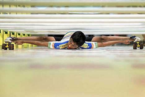 Maata viistäen. 11-vuotias intialainen Rohan Ajit Kokane esittelee taitojaan hongkongilaisessa kauppakeskuksessa järjestetyssä tapahtumassa. Hän alittaa esteet, joiden korkeus on vain 6,75 tuumaa (hieman yli 17 cm). Tapahtuman tarkoituksena oli kannustaa ikääntyviä ihmisiä harrastamaan liikuntaa. Ikääntyvät ihmiset eivät tosin tähän temppuun taida pystyä.