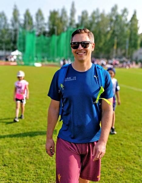 Joona Puhakka lastensa kanssa kentällä. Joel-poika pitää jalkapallosta.