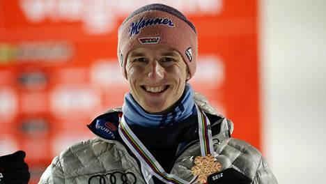 Karl Geiger poseeraa lentomäen maailmanmestarina Planicassa.