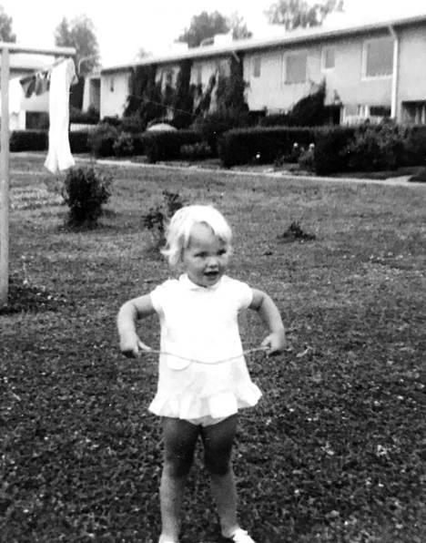 Eva Biaudet kotipihalla Kannelmäessä 60-luvulla. Rivitalon isoon pihapiiriin kuuluivat keinut ja uima-allas.