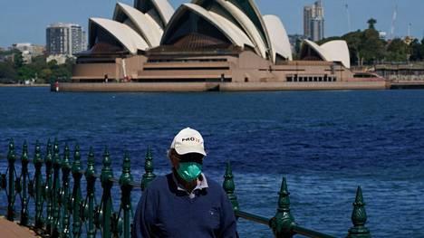 Kasvomaskia käyttävä mies kävelee Sydneyssä 6. lokakuuta 2021, taustalla kuuluisa oopperatalo.