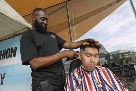 """Emmanuel """"Payo"""" Ampofo leikkaa Kietin, 22, hiuksia Oodin terassin kupeessa."""