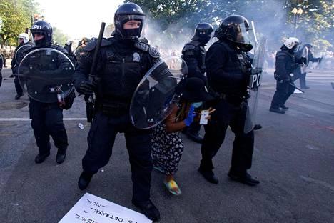 Mielenosoittaja yritti päästä poliisilinjan läpi Valkoisen talon lähellä.