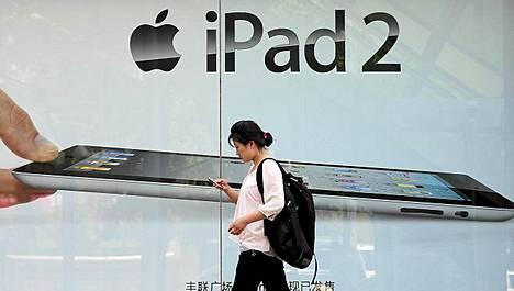 Nainen kävelee iPad-mainoksen ohi Pekingissä.