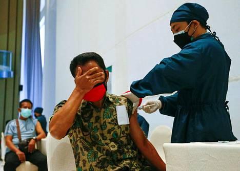 Mies peitti silmänsä saadessaan kiinalaisvalmisteisen Sinovac-koronarokotteen Jakartassa huhtikuussa.