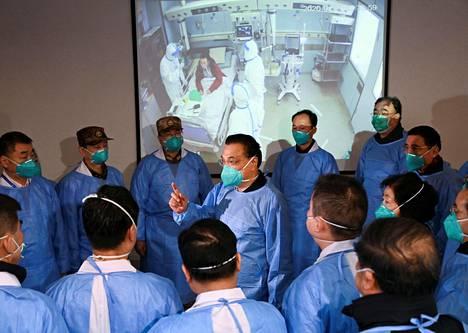 Kasvonsa maskilla suojannut Kiinan pääministeri Li Keqiang (keskellä) vieraili maanantaina sairaalassa Jinyintanissa.
