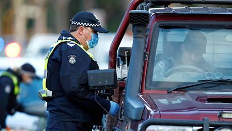 Poliisi tarkastaa autoja tarkastuspisteellä Melbournessa koronatartuntojen lähdettyä nousuun.