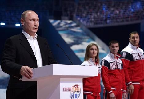 Presidentti Vladimir Putin puhui Sotshin olympialaisissa vierellään kehuttu taitoluistelujoukkue. Julia Lipnitskaja Putinin vieressä oikealla.