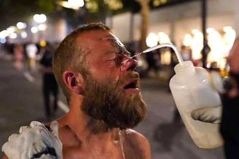 Kyynelkaasun huuhtominen silmistä onnistuu parhaiten, kun nestettä ruiskutetaan silmään kovalla paineella.