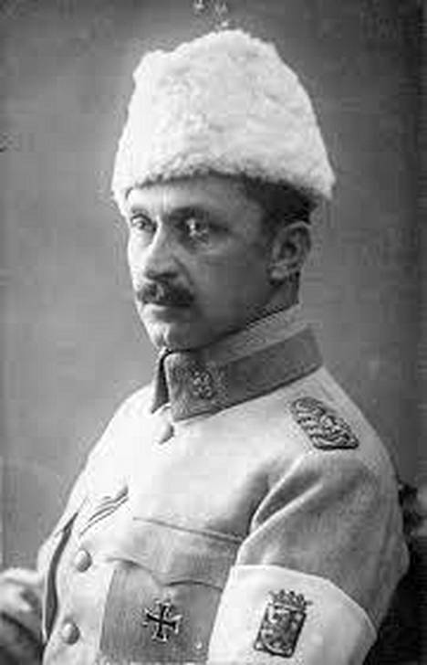 Ratsuväenkenraaliksi ylennetyllä Mannerheimilla on yllään harmaa sotilaspuku, käsivarressaan valkoinen nauha ja päässään valkea karvalakki. Rinnassa kiiltää vasta myönnetty Preussin 1. luokan rautaristi.