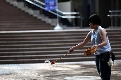 Japanilaisnainen roiski vettä kadulle Tokiossa maanantaina.