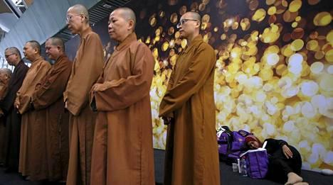 Buddhalaismunkit rukoilivat Kuala Lumpurin lentokentällä järjestetyssä rukoustilaisuudessa sunnuntaina.
