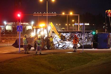 Kaatuneen vetoauton lastia purettiin ensin traktorikaivurilla, ennen kuin sitä saatiin yritettyä nostaa pystyyn.
