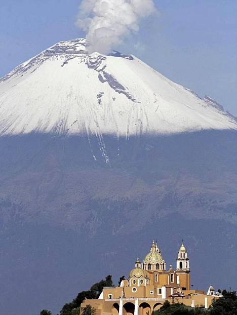 Meksikossa Pueblan laaksossa sijaitsevan kirkon takana nousee lumihuippuinen Popocatepetl-tulivuori.