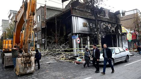 Miehet kävelivät mellakoiden yhteydessä poltetun pankin ohi pari viikkoa sitten Teheranissa.