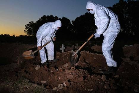 Hautausmaan työntekijoitä hautaamassa covid-19-tautiin kuollutta Rio de Janeirossa.