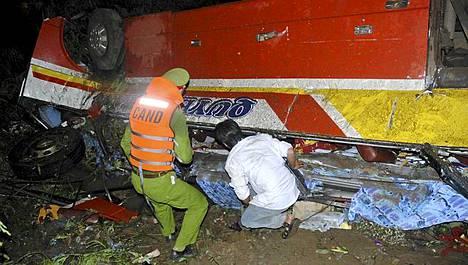 Pelastajat yrittivät löytää eloonjääneitä bussinromusta.