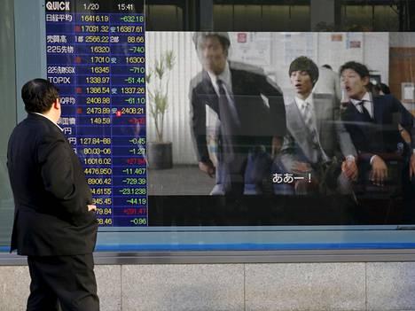 Mies seurasi kursseja valotaululta Japanin Tokiossa