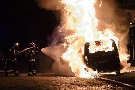 Palomiehet sammuttavat autoa lauantain vastaisena yönä.