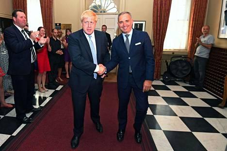 Tuore pääministeri Boris Johnson saapumassa pääministerin virka-asunnolle Downing Streetillä. Kuvan oikeassa laidassa Dominic Cummings taputtamassa.