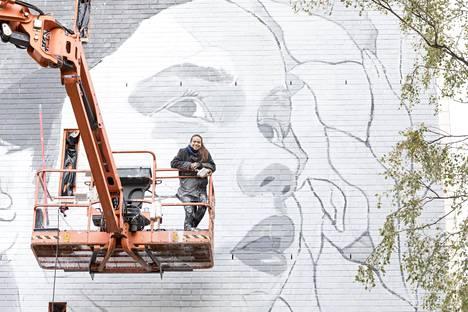 Sofia Marof kerrostalon seinässä muraalimaalari Paola Delfinin ikuistamana.