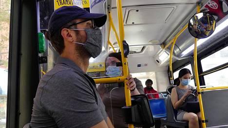 Matkustajat käyttivät kasvomaskeja bussissa New Yorkissa.