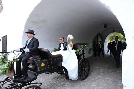 Hääpari kulki kirkolta juhlapaikalle juhlallisesti hevoskärryjen kyydissä.
