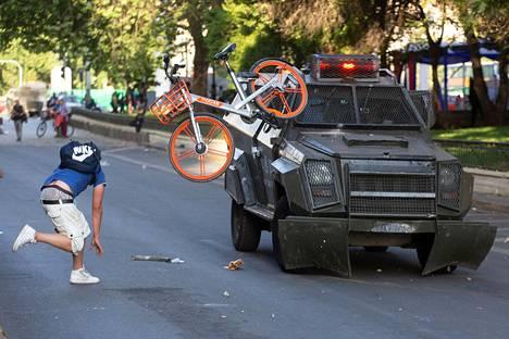 Mielenosoittaja heittää pyörän poliisiautoa kohti.
