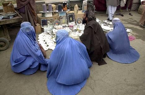Koko vartalon, pään ja kasvot peittävään burkaan pukeutuneita naisia torilla Kabulissa vuonna 2001.