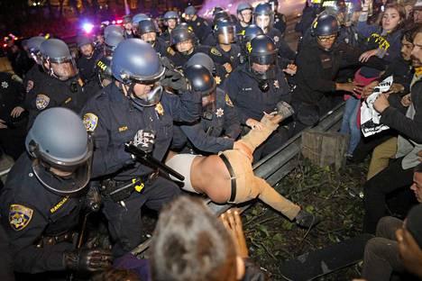 Seattle: Mellakkavarusteisiin sonnustautuneet poliisit ottivat kiinni mielenosoittajan.