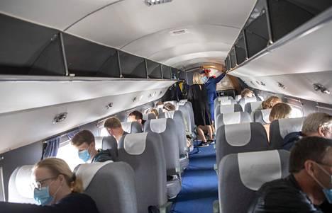 Matkustajat katsovat tiiviisti ulos. Lennoilla on tänä keväänä ja kesänä ollut koronavirusepidemian takia erityisjärjestelyjä, kuten se, että jokainen käyttää kasvomaskia.