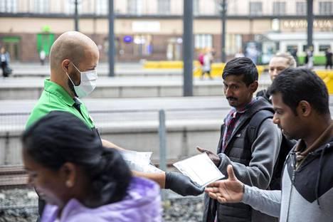 VR jakoi kertakäyttöisiä maskeja matkustajille perjantaiaamuna Helsingin rautatieasemalla.