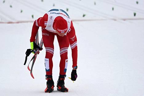 Alexander Bolshunov kävi poimimassa katkenneen sauvan palasia kisan jälkeen.