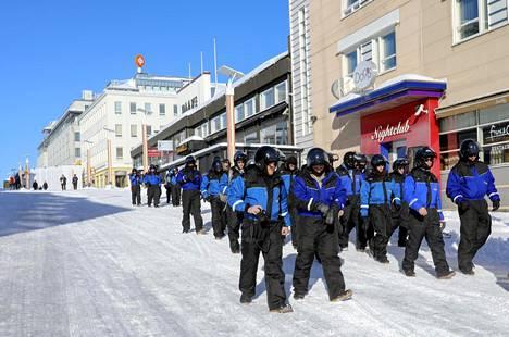 Moottorikelkkahaalareissa liikkuva turistilauma Rovaniemen keskustassa maaliskuussa.