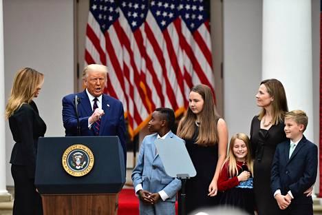 Amy Coney Barrett lastensa kanssa ruusupuutarhassa pidetyssä seremoniassa, jossa Trump nimitti hänet korkeimman oikeuden tuomariehdokkaakseen.