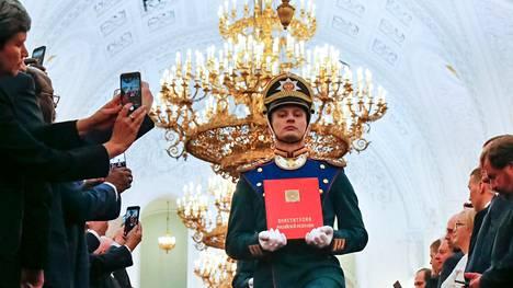 Kunniavartioston sotilas kantaa Venäjän perustuslakia kuvassa, joka on otettu presidentti Vladimir Putinin virkaanastujaisissa toukokuussa 2018.