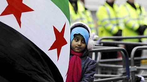 Tyttö Syyrian lipun kanssa Lontoossa, jossa osoitettiin mieltä lauantaina Syyrian nykyhallintoa vastaan.